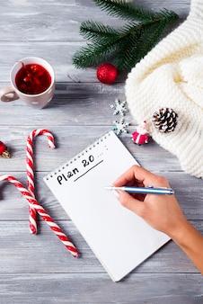 Hand des frauenschreibens auf notizblock weihnachtsgrüße mit tee, dekoration auf hölzernem