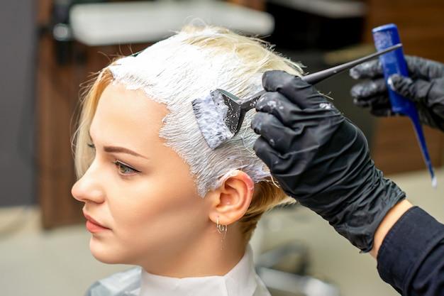 Hand des friseurs, der weiße farbe auf das haar des kunden im friseursalon aufträgt