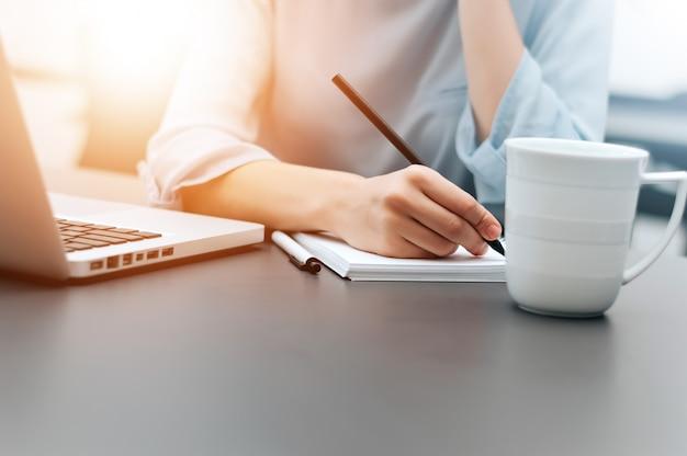 Hand des geschäftsfrauschreibens auf papier im büro.
