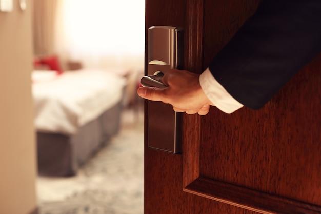 Hand des geschäftsmannes, der hotelzimmer öffnet