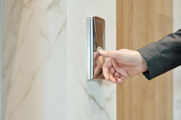 Hand des geschäftsmannes, der knopf an der wand drückt, während er durch tür steht und auf aufzug innerhalb des hotel- oder bürozentrums wartet