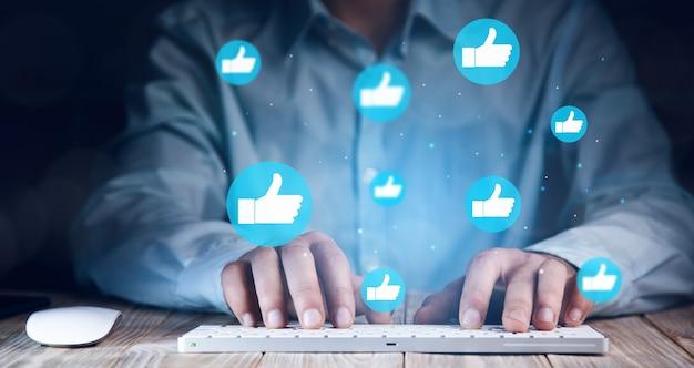 Hand des geschäftsmannes, der laptop mit symbol soziale medien und soziales netzwerk verwendet. online-marketing-konzept