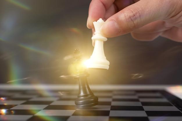 Hand des geschäftsmannes, der schachspielfigur im wettbewerbserfolgsspiel bewegt. strategie-, management- oder führungskonzept