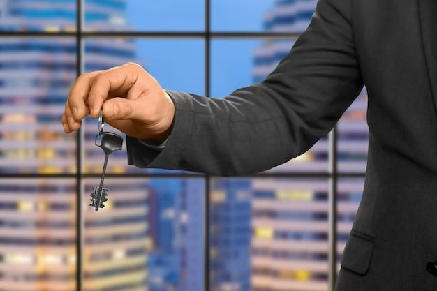Hand des geschäftsmannes, der schlüssel hält. immobilienmakler auf abendhintergrund. die neue wohnung gehört ihnen. besonderes geschenk für firmenmitarbeiter.