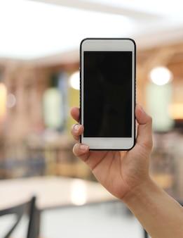 Hand des geschäftsmannes einen smartphone im leeren schwarzen schirm halten