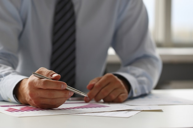 Hand des geschäftsmannes in der klage, die mit füllt und unterzeichnet