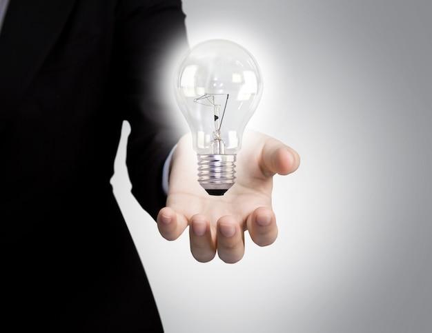 Hand des geschäftsmannes neben einer glühbirne