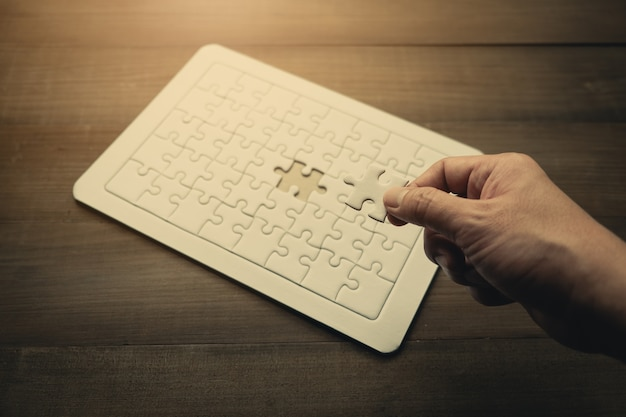 Hand des geschäftsmannes puzzlespiel des letzten stückes, geschäftserfolgkonzept halten