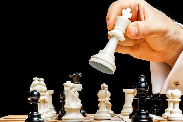 Hand des geschäftsmannes schach spielend