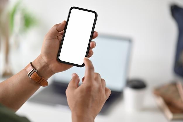 Hand des geschäftsmannes unter verwendung des intelligenten telefons des leeren weißen schirmes.