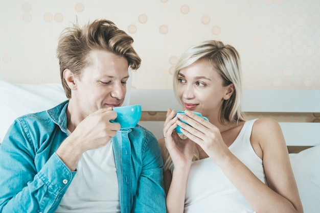 Hand des glücklichen paars, die morgens schale hält und kaffee trinkt