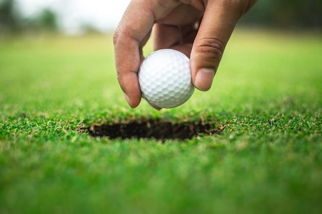 Hand des golfers, der golfballformloch hält