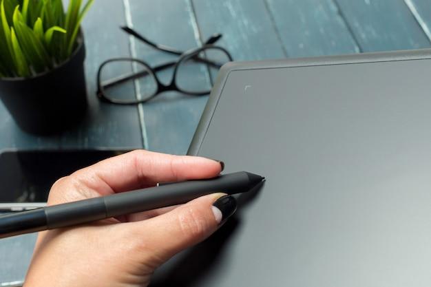 Hand des grafikdesigners arbeitend mit stilus und tablette