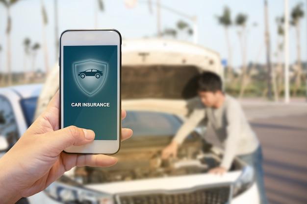 Hand des gutaussehenden mannes, die smartphone hält, um autoversicherungsanwendung online nach seinem defekten auto zu benutzen. versicherungskonzept