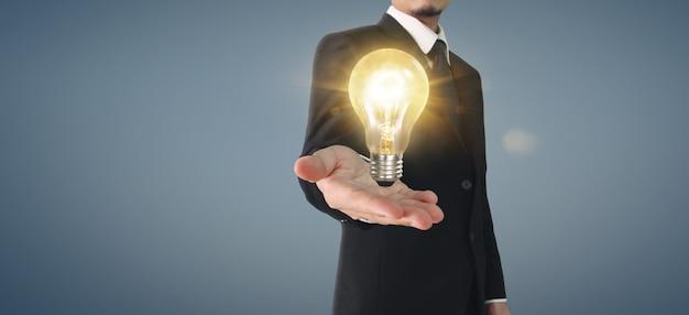Hand des haltens der beleuchteten glühbirne. innovationsinspirationskonzept