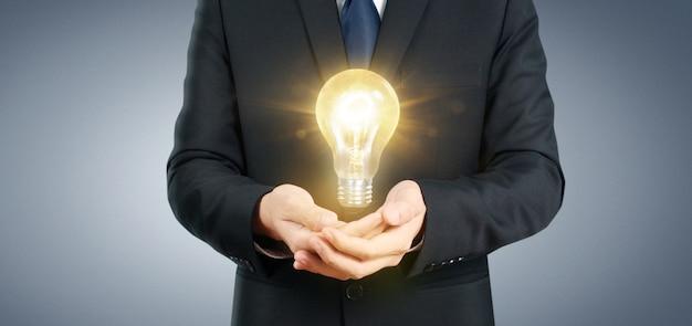 Hand des haltens der belichteten glühlampe, ideeninnovations-inspirationskonzept