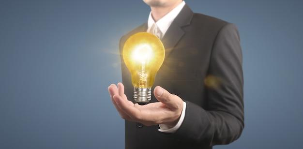 Hand des haltens einer beleuchteten glühbirne, idee, innovationsinspirationskonzept