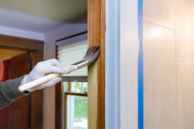 Hand des handwerkers, der mit handschuhen in einem pinsel malt, der lackfarbe aufträgt holztüren, die zierleisten mit pinsel auftragen