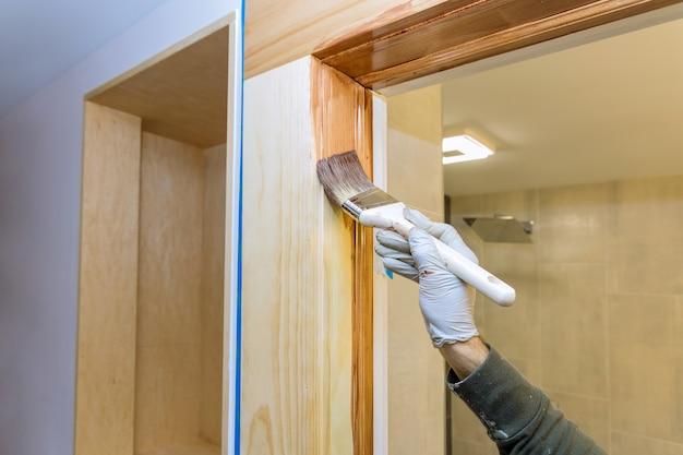 Hand des handwerkers malen mit handschuhen in einem pinsel, der lackfarbe holz aufträgt