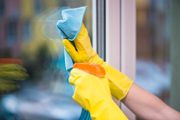Hand des hausmeisters, der glasfenster mit stoff säubert