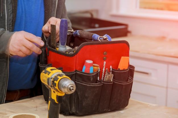 Hand des heimwerkers mit einer werkzeugtasche.