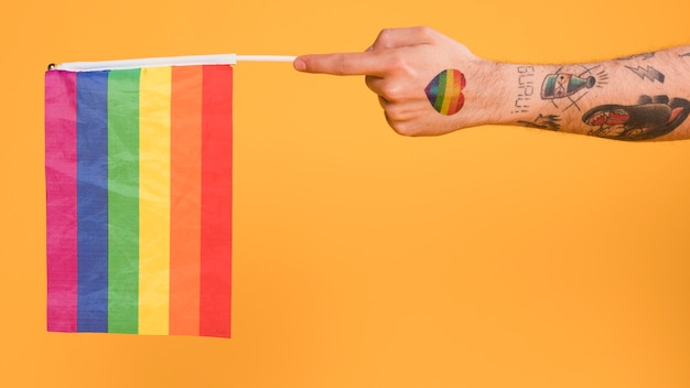 Hand des homosexuellen mannes, der lgbt-flagge hält