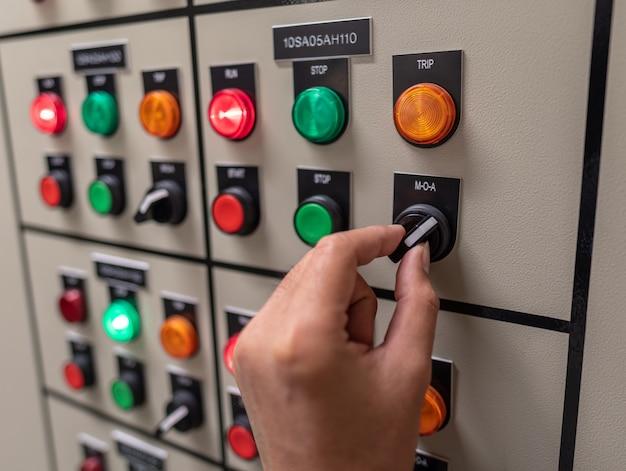Hand des ingenieurs, der arbeitet und die elektrische energieverteilung der schaltanlage im umspannwerkraum überprüft