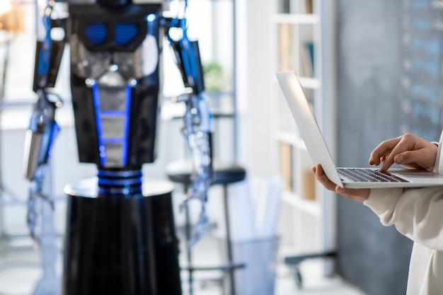 Hand des jugendlichen studenten oder programmierers, der neue software entwickelt oder über technisches projekt mit roboter auf hintergrund arbeitet
