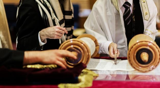 Hand des jungen, der das jüdische torah bei bar mizwa liest