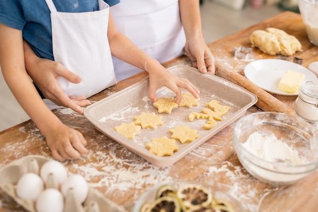 Hand des jungen, der rohe kekse auf tablett setzt, während mutter mit teig und keksen durch küchentisch hilft