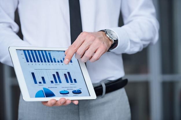 Hand des jungen eleganten ökonomen oder des analytikers in der formellen kleidung, die auf finanzdiagramm in tablette zeigt, während präsentation macht