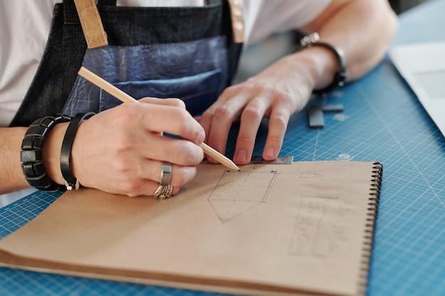Hand des jungen handwerkers mit bleistift über seite des notizblocks beim zeichnen der skizze des gegenstands, um für einen seiner kunden zu machen