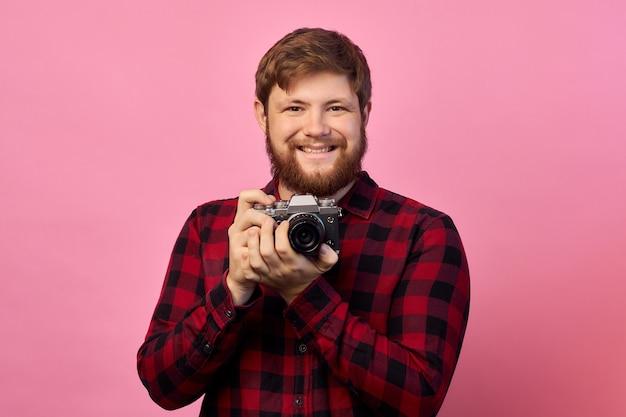 Hand des jungen hispanischen mannes, der weinlesekamera über lokalisiertem rosa hintergrund hält