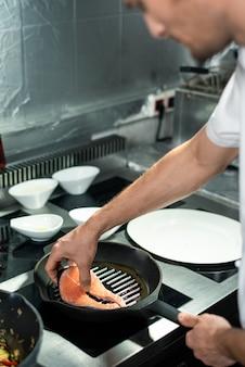 Hand des jungen kochs, der ein stück lachs auf eine heiße pfanne mit olivenöl legt, während er am elektroherd steht und fisch und gemüse kocht