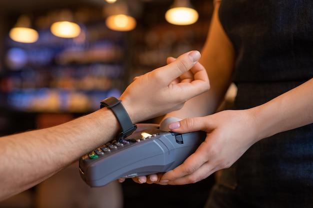 Hand des jungen kunden des cafés oder des restaurants, der arm mit smartwatch über zahlmaschine hält, während für getränk oder essen bezahlt