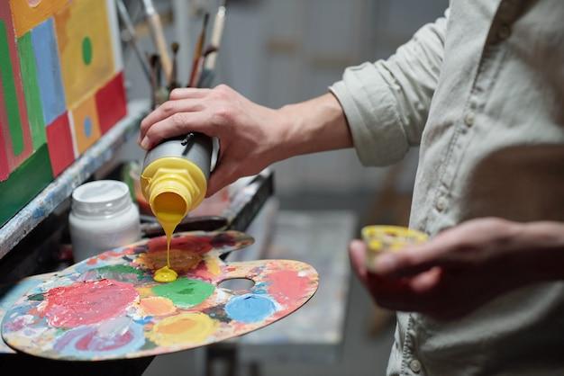 Hand des jungen malers, der gelbe farbe auf palette hinzufügt, bevor man anfängt zu malen, während man vor staffelei im atelier der künste steht