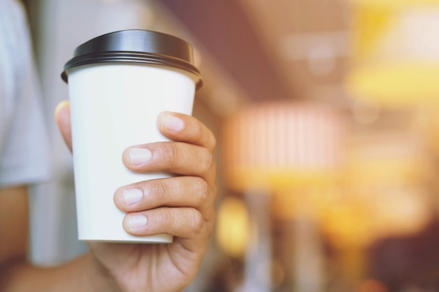 Hand des jungen mannes, der pappbecher des wegnehmenden kaffeetrinkens heiß auf dem hölzernen tisch im café-kaffeehaus hält.