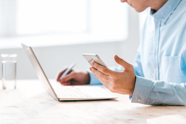 Hand des jungen mannes, der smartphone über tisch hält, während er vor laptop sitzt und arbeitsnotizen macht