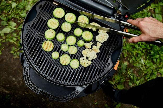 Hand des jungen mannes, der zucchinigemüse auf großem gasgrill grillt.