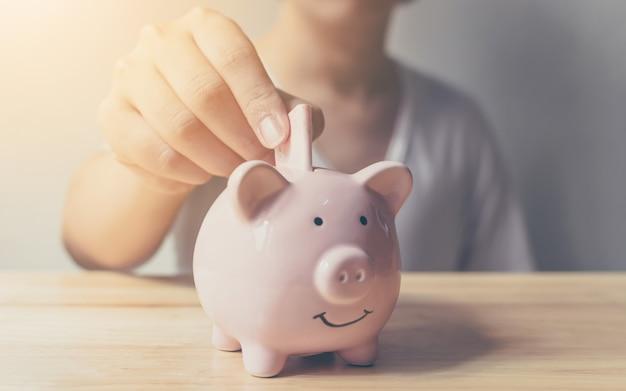 Hand des jungen mannes, die banknote in sparschwein einsetzt. einsparungsgeldkonzeptfinanzgeschäftsinvestition