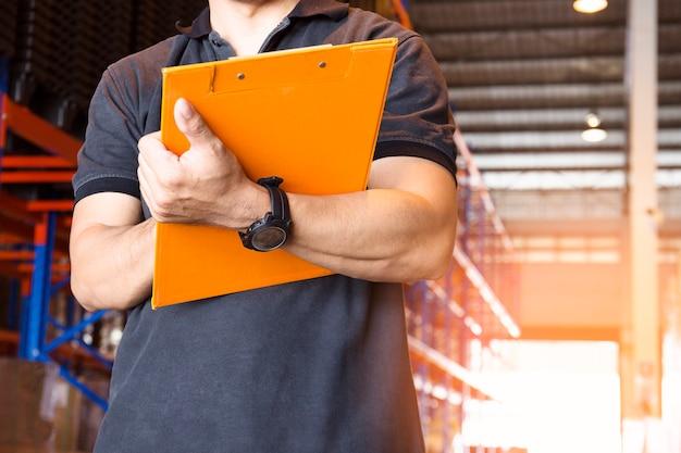 Hand des jungen mannes, die klemmbrett mit inventar das produkt im lager hält.