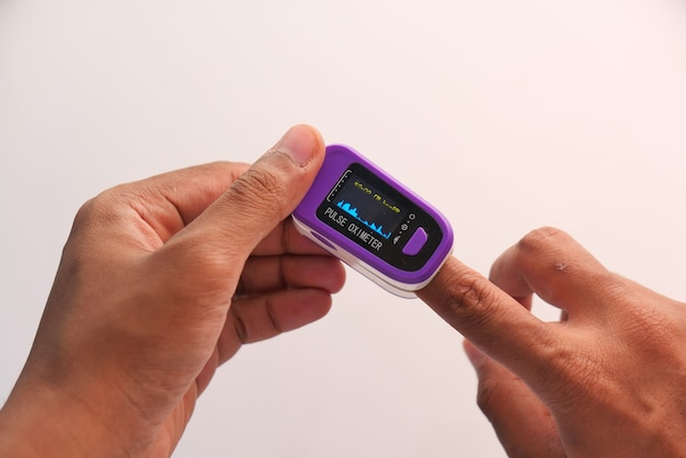 Hand des jungen mannes unter verwendung des pulsoximeters