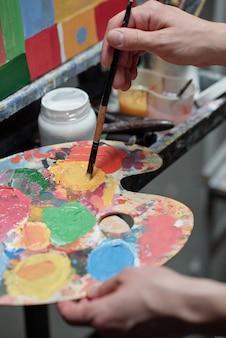 Hand des jungen professionellen malers, der farben auf palette mischt, während er vor staffelei mit unvollendetem bild steht
