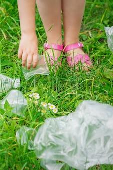 Hand des kindes reinigt grünes gras von plastikmüll