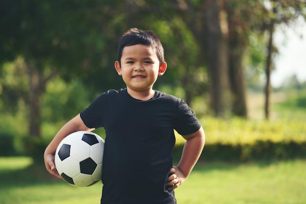 Hand des kleinen jungen, die fußballfußball hält