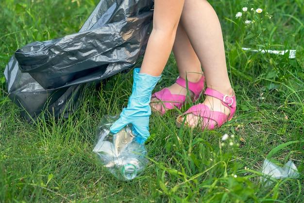 Hand des kleinen mädchens, das gebrauchte plastikflasche für das reinigen des parks aufhebt.
