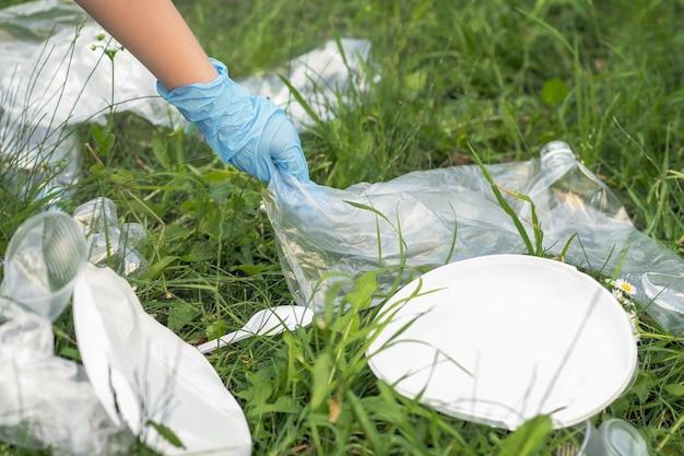 Hand des kleinen mädchens, das müllplastik für das reinigen des parks aufhebt