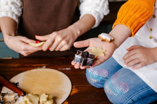 Hand des kleinen mädchens, die traditionelle weihnachtsplätzchen macht
