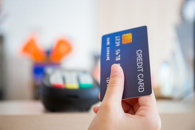 Hand des kunden mit kreditkarten-verschwommenem kreditkartenlesegerät am bartheke