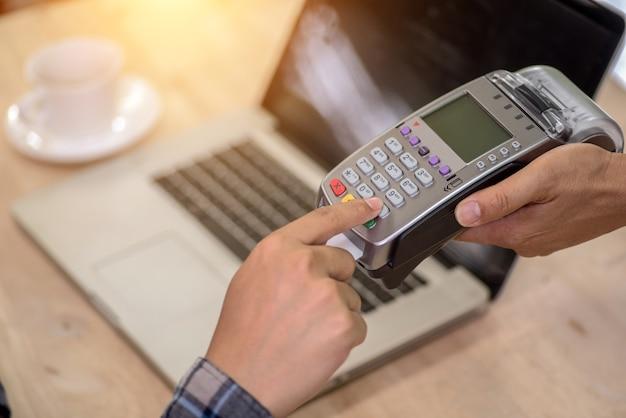 Hand des kunden zahlend mit kontaktloser kreditkarte mit nfc-technologie.